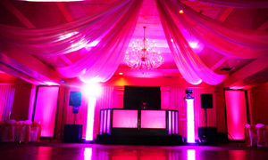 LED Uplights create an ambiance in an elegant Ballroom Wedding